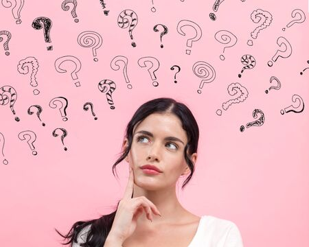 Small question marks with young woman in thoughtful pose Stock Photo