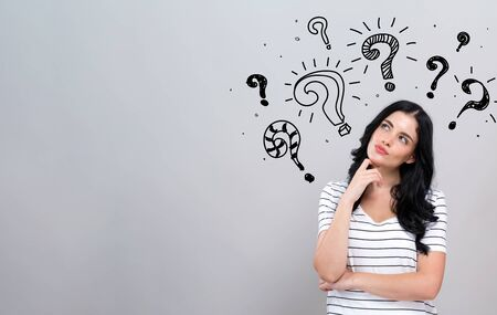 Question marks with young woman in a thoughtful face Stock Photo