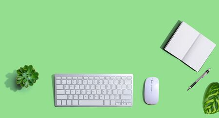 Computer keyboard and mouse with notebook from above