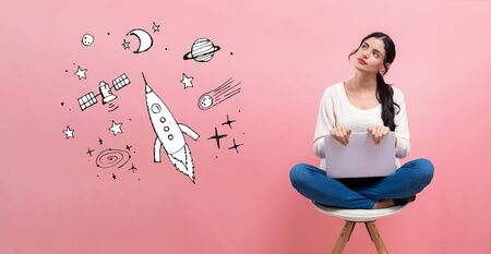 Dream of space and rocket with young woman using a laptop computer