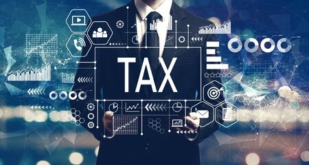 Tax theme with businessman holding a tablet computer Stock Photo