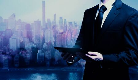 Businessman holding a tablet computer in a city background 스톡 콘텐츠 - 138475116