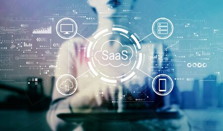 SaaS - software as a service concept with businesswoman using a tablet on a city background Stock Photo