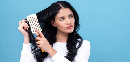 Beautiful young woman holding a hairbrush on a blue background 版權商用圖片