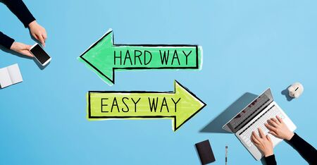 Hard way or easy way with people working together with laptop and phone