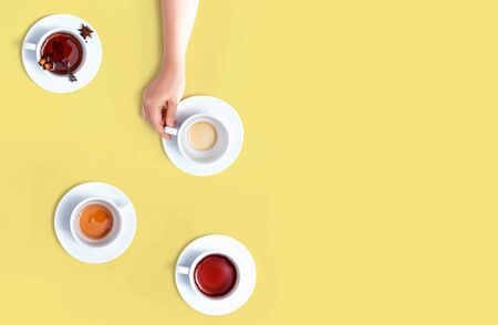 Female hand holding a tea cup overhead view - flat lay