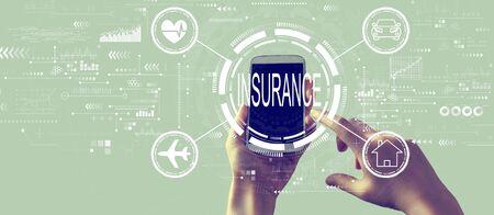 Insurance concept with person holding a white smartphone Foto de archivo