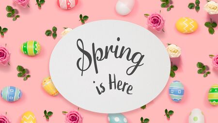Spring is here message with Easter eggs on a pink background