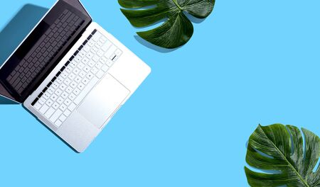 Laptop computer with tropical plants - flat lay