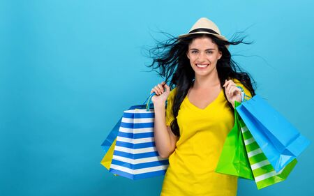 Woman with many shopping bags on a blue background