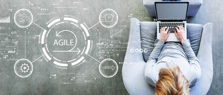 Agile concept with man using a laptop in a modern gray chair Foto de archivo