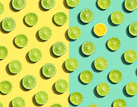 One out unique lemon surrounded by limes - flat lay Stock Photo