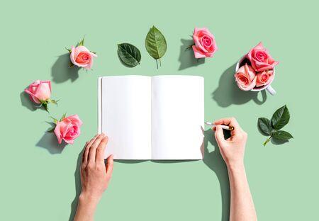 文字在有桃红色玫瑰的一本笔记本的妇女赤塑顶视图