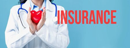 Insurance theme with a doctor holding a heart on a blue background Stock Photo