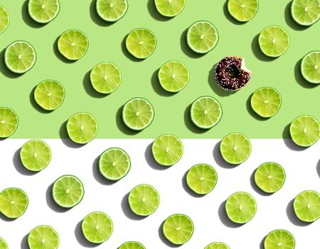 One out unique donut surrounded by limes - flat lay Stock Photo