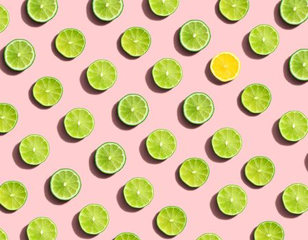 One out unique lemon surrounded by limes - flat lay Standard-Bild