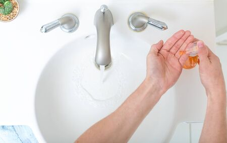 Person washing their hands at with soap and water for coronavirus prevention Standard-Bild