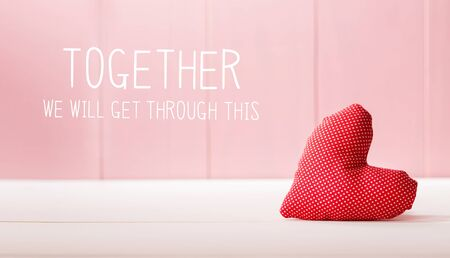 Together We Will Get Through This message with a red heart cushion over a pink wooden wall