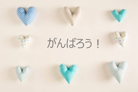 Fight together in Japanese language with blue heart cushions on a white paper background