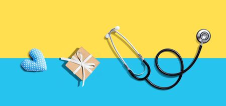 Stethoscope with a gift and a heart cushion - flat lay Standard-Bild