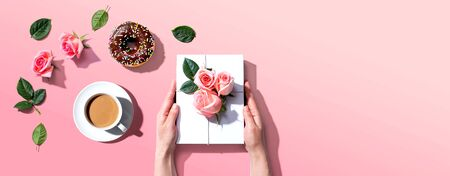 Female hands holding a gift box with pink roses overhead view - flat lay