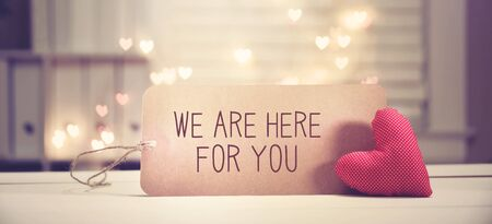 We are Here for You message with a red heart with heart shaped lights Stock Photo