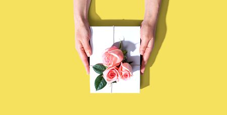 女性手中拿着一个带有粉红色玫瑰的礼品盒俯视——平躺着