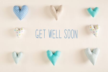 Get well soon message with blue heart cushions on a white paper background