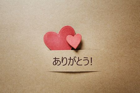 Arigato - Thank you in Japanese language with handmade small paper hearts Imagens