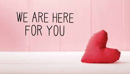 We are Here for You message with a red heart cushion over a pink wooden wall