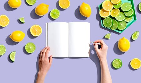 Person writing in a notebook with lemons and limes