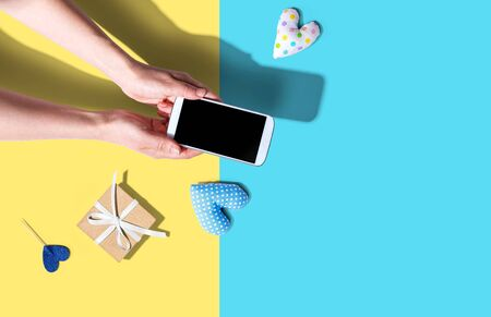 Woman holding her smartphone with small gift and heart cushions from above Standard-Bild
