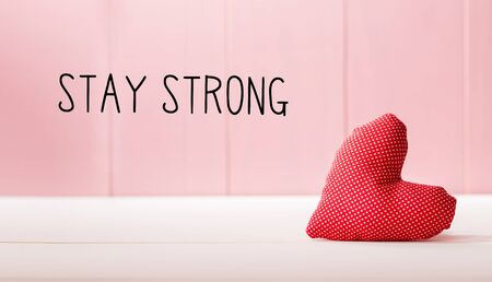 Stay Strong message with a red heart cushion over a pink wooden wall Banco de Imagens