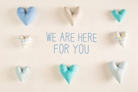 We are Here for You message with blue heart cushions on a white paper background