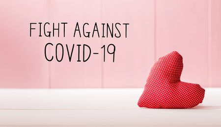 Fight Against Covid-19 message with a red heart cushion over a pink wooden wall