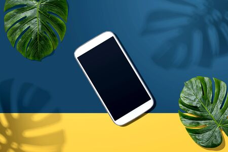 Smartphone with tropical monstera leaves and shadow - flat lay