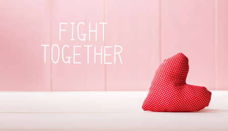 Fight Together message with a red heart cushion over a pink wooden wall