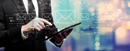 Email concept with businessman using his tablet computer