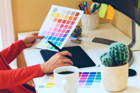 Graphic designer using her graphic tablet in a home office