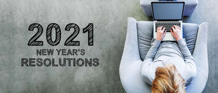2021 New Years Resolutions with man using a laptop in a modern gray chair