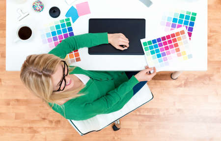 Graphic designer using her graphic tablet in her home office 版權商用圖片