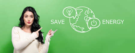 Save energy concept with young woman pointing on a green background Фото со стока