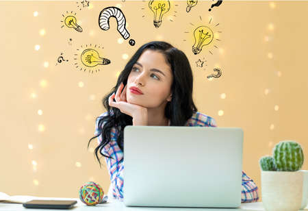 Question with light bulbs with young woman using a laptop