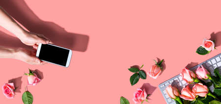 Woman holding her smartphone with pink roses overhead view - flat lay