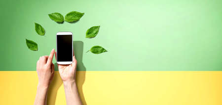Person holding a smartphone with green leaves Фото со стока