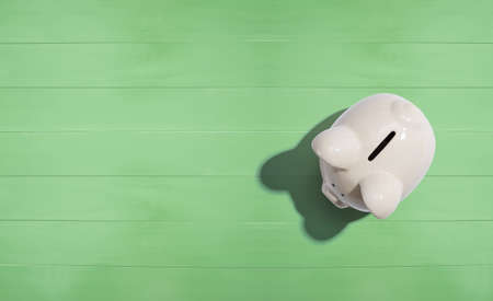 A white piggy bank overhead view flat lay