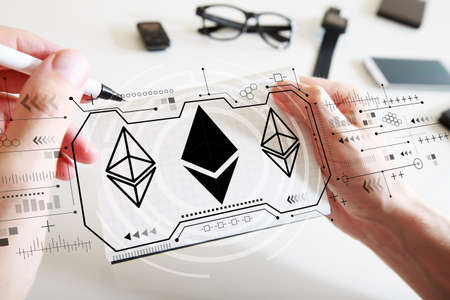 Ethereum with man writing in a notebook Фото со стока