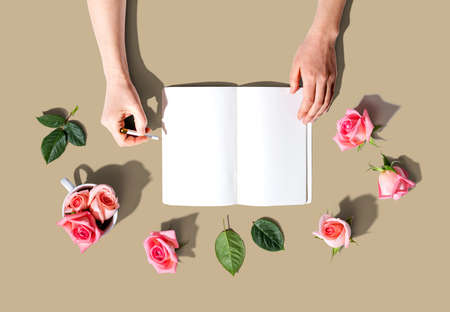 Woman writing in a notebook with pink roses overhead view