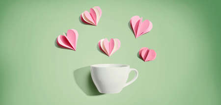 Coffee cup with paper craft hearts - flat lay