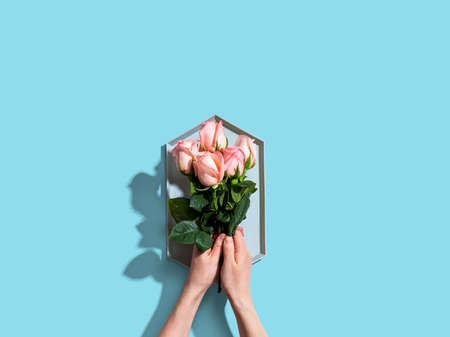 Woman holding pink roses overhead view - flat lay